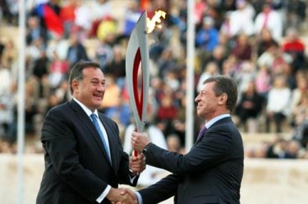 The Flame is passed from HOC President Spyros Caprolos to Russias Deputy Prime Minister Dmitry Kozak